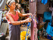 27 AUGUST 2016 - BANGKOK, THAILAND: A woman hangs her laundry to dry in the Pom Mahakan slum community. The Pom Mahakan community is known for fireworks, fighting cocks and bird cages. Mahakan Fort was built in 1783 during the reign of Siamese King Rama I. It was one of 14 fortresses designed to protect Bangkok from foreign invaders. Only two of the forts are still standing, the others have been torn down. A community developed in the fort when people started building houses and moving into it during the reign of King Rama V (1868-1910). The land was expropriated by Bangkok city government in 1992, but the people living in the fort refused to move. In 2004 courts ruled against the residents and said the city could evict them. The city vowed to start the evictions on Sept 3, 2016, but this week Thai Prime Minister Gen. Prayuth Chan-O-Cha, sided with the residents of the fort and said they should be allowed to stay. Residents are hopeful that the city will accede to the wishes of the Prime Minister and let them stay.       PHOTO BY JACK KURTZ