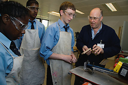 Woodwork teacher showing students how to make a wooden joint  in a Design technology lesson,