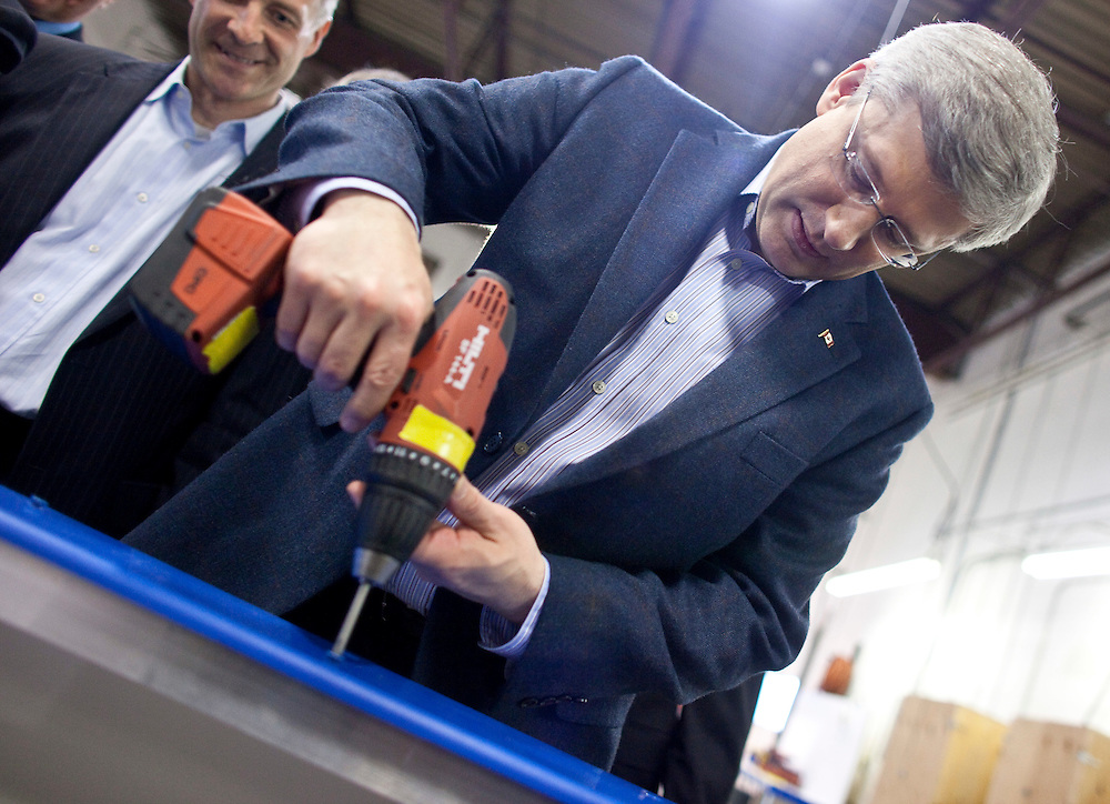 Conservative leader Stephen Harper screws in the dasher for some hockey boards during a campaign stop at Sport Systems Unlimited in Waterloo, Ontario, April 27, 2011. <br /> AFP/GEOFF ROBINS/STR