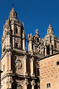 """Low angle view of Clerecia Church,  Salamanca, Spain, pictured on December 18, 2010 at midday with the Casa de las Conchas in the foreground. The Baroque style Clerecia Church, originally the Royal College of the Company of Jesus, was commissioned in the 17th century, from architect Juan Gomez de Mora, by Queen Margarita of Austria, wife of Philip III of Spain. It comprises two sections: the Jesuit school and church, with its three-storey Baroque cloister, and private living quarters for the monks and now houses the Salamanca Pontificia University. Salamanca, an important Spanish University city, is known as La Ciudad Dorada (""""The golden city"""") because of the unique golden colour of its Renaissance sandstone buildings. Founded in 1218 its University is still one of the most important in Spain. Around it the Old Town is a UNESCO World Heritage Site. Picture by Manuel Cohen"""
