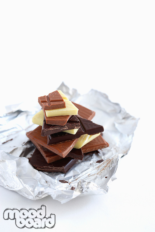 Stack of different chocolate pieces on aluminum foil  studio shot