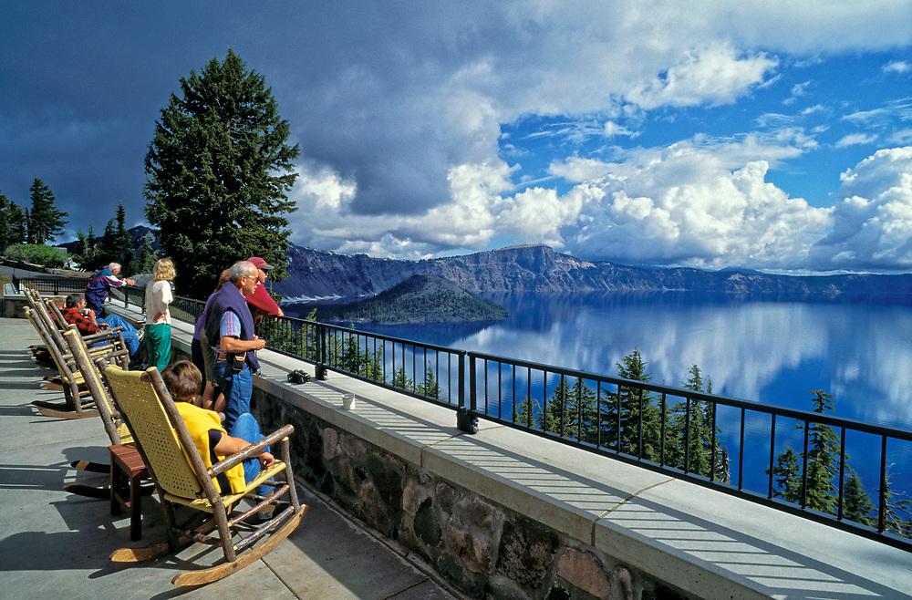 Visitors at Crater Lake Lodge enjoying view of Crater Lake and Wizard Island; Crater Lake National Park, Oregon.