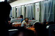 Passengers sleep in the dining car. By paying extra they have a place to sleep when the rest of the train is standing room only. Qinghai, China. 2006