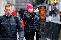 © Licensed to London News Pictures. 30/11/2017. London, UK. A woman films a light snowfall in central London on Thursday, 30 November 2017. Photo credit: Tolga Akmen/LNP
