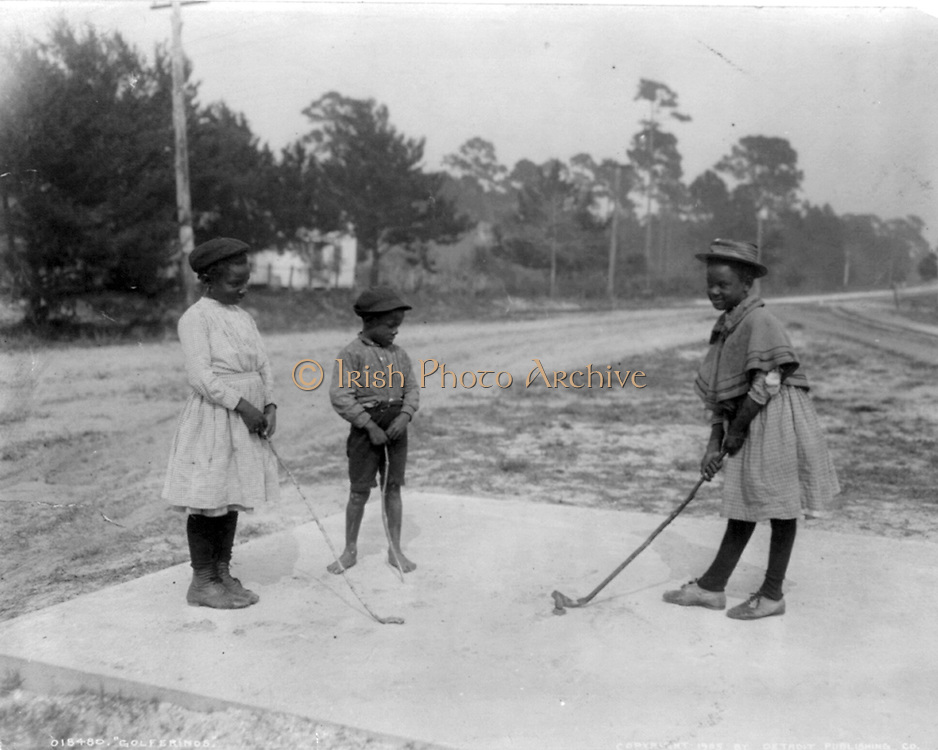 Three African American children playing golf with clubs made of sticks.   c1905.