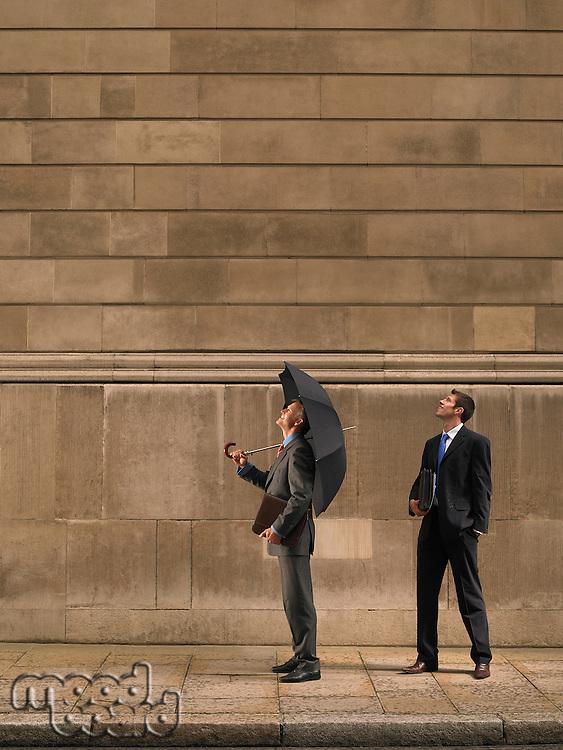 Two men on sidewalk looking up