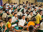 06 NOVEMBER 2014 - SITTWE, RAKHINE, MYANMAR: Boys in a school for Rohingya IDPs sit on the floor in the classroom. After sectarian violence devastated Rohingya communities and left hundreds of Rohingya dead in 2012, the government of Myanmar forced more than 140,000 Rohingya Muslims who used to live in and around Sittwe, Myanmar, into squalid Internal Displaced Persons camps. The government says the Rohingya are not Burmese citizens, that they are illegal immigrants from Bangladesh. The Bangladesh government says the Rohingya are Burmese and the Rohingya insist that they have lived in Burma for generations. The camps are about 20 minutes from Sittwe but the Rohingya who live in the camps are not allowed to leave without government permission. They are not allowed to work outside the camps, they are not allowed to go to Sittwe to use the hospital, go to school or do business. The camps have no electricity. Water is delivered through community wells. There are small schools funded by NOGs in the camps and a few private clinics but medical care is costly and not reliable.   PHOTO BY JACK KURTZ