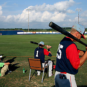 Clarinda A's Ryan Peterson, right, and Seve Alvarez, sitting, check their bat positions as they wait for the start of their tournament game last July.  photo by David Peterson