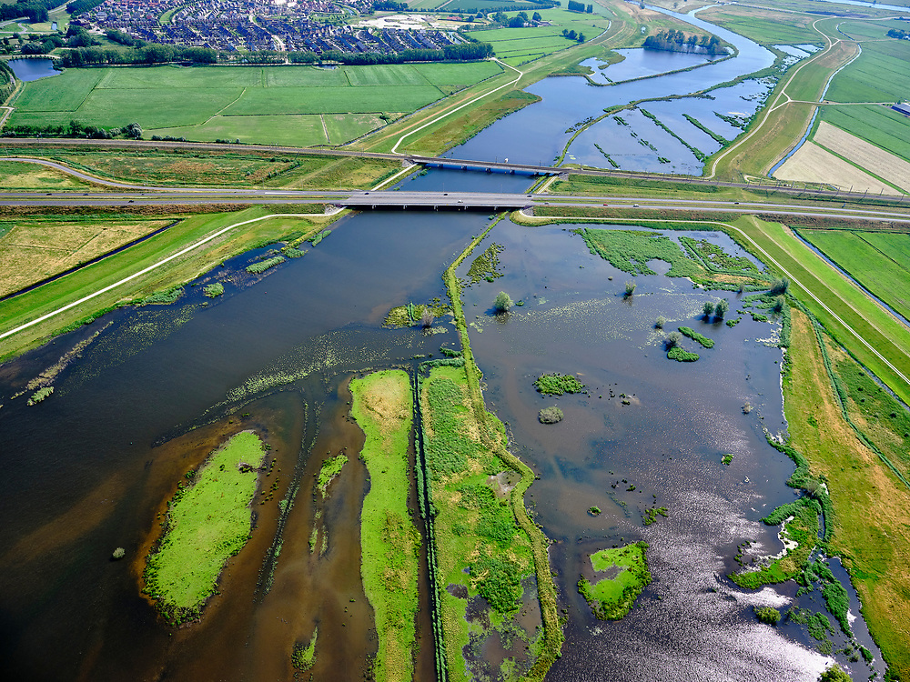 """Nederland, Overijssel, Gemeente Kampen; 21–06-2020; het Reevediep richting IJssel, gezien vanaf natuurgebied De Enk (rechtsonder). In het midden de Reevediepbrug(rijksweg N50en parallel deSpoorbrug Reevediep.<br /> Het Reevediep is aangelegd in het kader van het project Ruimte voor de Rivier om bij hoogwater water af te voeren voordat dit het nabij gelegen Kampen bereikt, direct naar het IJsselmeer, de 'bypass Kampen'. Het Reevediepgebied is ook een natuurgebied en vormt een ecologische verbindingszone tussen rivier de IJssel en Drontermeer.<br /> Reevediep towards IJssel, seen from De Enk nature reserve (bottom right). In the middle the Reevediep Bridge with parallel the Reevediep Railway Bridge.<br /> Reevediep in the direction of river IJssel, seen from the mouth of the Reevediep.<br /> The Reevediep has been constructed as part of the Room for the River project, and functions to discharge high waters before reaching the nearby Kampen, directly to the IJsselmeer, the """"bypass Kampen"""". The Reevediep area is also a nature reserve and forms an ecological connecting zone between the river IJssel and Drontermeer.<br /> <br /> luchtfoto (toeslag op standard tarieven);<br /> aerial photo (additional fee required)<br /> copyright © 2020 foto/photo Siebe Swart"""