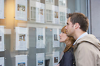 Couple looking in window outside estate agents