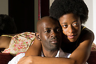 African American woman hugging her South African husband as he sits in an upholstered chair.  Both look peaceful and content.