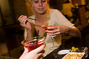 "A young lady from the US finishes stirring her vodka and cranberry juice cocktail and is about to sip her expensive drink at the bar of the Sphere Bar at Heathow Airport's Sofitel Hotel at Terminal 5. Drinking with an unseen friend whose hand we see in the lower part of the picture, the girl raises her conical glass to sip the alcoholic beverage before proposing a toast to their unforeseen night's stay in this luxury hotel after a cancelled flight. Some nuts are on a small dish which are largely untouched. From writer Alain de Botton's book project ""A Week at the Airport: A Heathrow Diary"" (2009)."