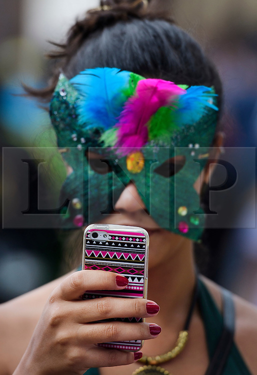 © Licensed to London News Pictures. 29/08/2016. London, UK. A carnival goer using a brightly coloured mobile phone while enjoying day two of the Notting Hill carnival, the second largest street festival in the world after the Rio Carnival in Brazil, attracting over 1 million people to the streets of West London.  Photo credit: Ben Cawthra/LNP