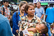 09 JULY 2014 - ARANYAPRATHET, SA KAEO, THAILAND: A Cambodian migrant are her son arrive at the immigration station in Aranyaprathet in a  Thai police truck. The Thai government has opened a One Stop Service Center in Aranyaprathet on the Thai-Cambodian border. More than 200,000 Cambodian migrant workers, most undocumented, fled Thailand in early June fearing a crackdown by Thai authorities after a coup unseated the elected government. Employers have been unable to fill the vacancies created by the Cambodian exodus and the Thai government has allowed them to return. The Cambodian workers have to have a job and their employers have to vouch for them. The Thai government is issuing temporary ID cards to allow them to travel openly to their jobs. About 800 Cambodian workers came back to Thailand through the Aranyaprathet border crossing Wednesday. The Thai government has opening similar service centers at three other crossing points on the Thai-Cambodian border.    PHOTO BY JACK KURTZ