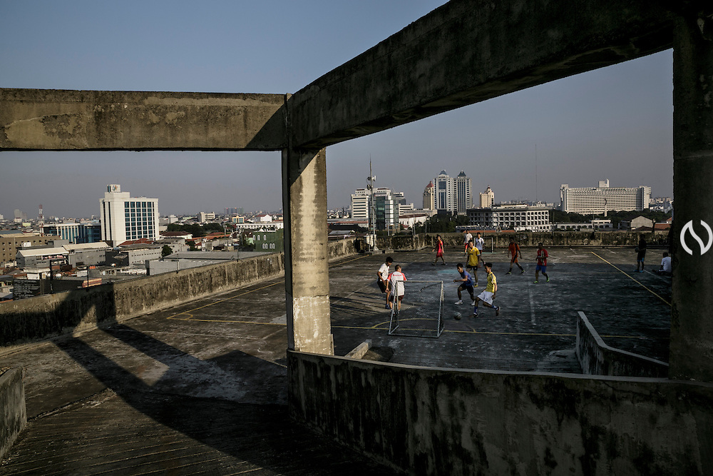 JAKARTA - INDONESIA; FRIDAY, SEPTEMBER 19, 2014; INDONESIA ECONOMIC RISING: Workers of a building play futsal on the rooftop of Istana building in Pasar Baru, Central Jakarta, Jakarta, Indonesia on Friday September 19, 2014. According to Asian Development Bank's 2014 report, Indonesia economy growth potential is in creative industry after for years relies heavily on natural resources such as mineral mining and palm oil. By the presidency of Joko Widodo, as a product of the third people election after the People Power Revolution in 1998, Indonesia is more confident in the economy growth and optimistic to become equal in quality to Brazil and China's economy growth. The emerging of Indonesia economy for the last one and a half decade after the end of Suharto's Dictatorship has been in significant way, the per capita growth has reached 400% under Susilo Bambang Yudhoyono presidency. Indonesia is home for 74 million of middle class as estimated by Boston Consulting Group, and  will double in 2020.