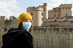 © Licensed to London News Pictures. 16/03/2020. London, UK. A woman wearing a face mask seen in front of a very quiet and empty Tower of London today which is normally busy with tourists at this time (11:50am). New cases and fatalities resulting from the COVID-19 strain of the Coronavirus continue to be reported daily in the UK with major sporting fixtures cancelled and people advised to stay at home if they have a cough and high temperature. Photo credit: Vickie Flores/LNP