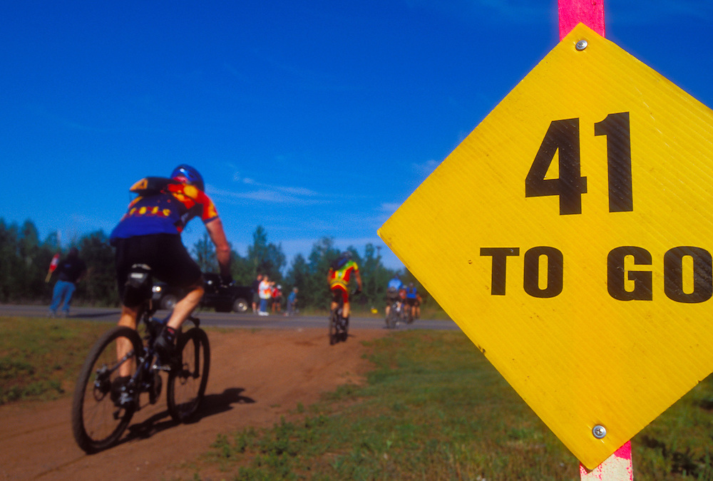 Mountain bikers in the Ore to Shore race pass a mileage sign near the start of the race in Ishpeming, Mich.