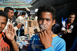 A boy smokes a cigarette at the Suq al-Guma, the Friday market in Cairo.