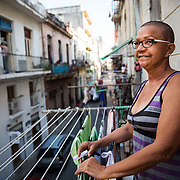 "03/11/2017  OLD HAVANA, CUBA     Elena Suarez (cq) 59, stands on the balcony of her home on Villegas Street in Old Havana, Cuba. Suarez had a brain tumor removed in February and offered coffee to passing tourists below in order to ""meet new people.""  (Aram Boghosian for The New Orleans Advocate)"