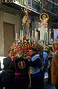 Statues of Catholic saints being carried in a religious procession through the back streets of Palermo