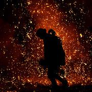 Men launch handheld fireworks known as tezutsu hanabi at Inaba Shrine in Gifu, Japan.