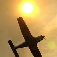 A Division of Forestry aircraft flies through the smoke surveying the area of  damage from a wildfire that burned up approximately  200 acres in Polk County, Fla. on Friday, Jan., 26, 2000 near Polk City, Fla. (AP Photo/Scott Audette)