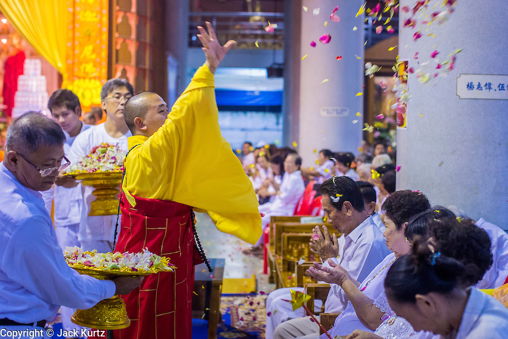 23 OCTOBER 2012 - HAT YAI, SONGKHLA, THAILAND: The abbot throws blessed flower petals to the crowd during a special service on the last day of the Vegetarian Festival at Wat Ta Won Vararum, a Chinese Buddhist temple in Hat Yai. The Vegetarian Festival is celebrated in Thai-Chinese communities throughout Thailand. It is the Thai Buddhist version of the The Nine Emperor Gods Festival, a nine-day Taoist celebration celebrated in the 9th lunar month of the Chinese calendar. For nine days, those who are participating in the festival dress all in white and abstain from eating meat, poultry, seafood, and dairy products. Vendors and proprietors of restaurants indicate that vegetarian food is for sale at their establishments by putting a yellow flag out with Thai characters for meatless written on it in red.  PHOTO BY JACK KURTZ