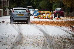 © Licensed to London News Pictures . 09/11/2013 . Manchester , UK . Cars carefully drive along hail-covered roads in Salford . A freak hail storm in Manchester covers the streets with large hailstones as loud rolling thunder is heard . Photo credit : Joel Goodman/LNP