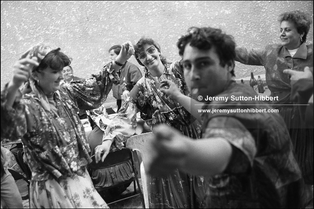 ROMANIAN VILLAGERS CELEBRATE WITH THE GYPSIES. THE TWO WOMEN ON THE LEFT HAVE BEEN DRESSED IN GYPSY CLOTHES BY THE GYPSY WOMEN. ROMANIAN ORTHODOX EASTER CELEBRATIONS. SINTESTI, ROMANIA. MAY 1997..©JEREMY SUTTON-HIBBERT 2000..TEL./FAX.+44-141-649-2912..TEL.  +44-7831-138817.