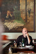 "Gast im ber¸hmten Kaffeehaus SLAVIA in der Prager Innenstadt. Im Hintergrund das Gem‰lde ""Der Absinthtrinker"" von Maler Viktor Oliva.<br /> <br /> Visitor at the famous CafÈ Slavia in the city centre of Prague. In the back a painting by Viktor Oliva with the title the Absinth drinker."
