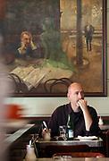 "Gast im ber¸hmten Kaffeehaus SLAVIA in der Prager Innenstadt. Im Hintergrund das Gem‰lde ""Der Absinthtrinker"" von Maler Viktor Oliva.<br /> <br /> Visitor at the famous CafÈ Slavia in the city centre of Prague. In the back a painting by Viktor Oliva with the title the Absinth drinker."