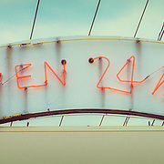 Faded neon sign advertising open 24 hours