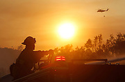 May 15, 2014 - Escondido, California, U.S -<br /> <br /> California Wildfires 2014 - Cocos Fire<br /> <br /> As the sun sets, Monrovia firefighter HAROL KALIMAN hoses water on a home that burned down as helicopters continue to do water drops in the area on Mount Whitney Road just west of Escondido on Thursday.<br /> ©Exclusivepix
