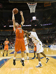 Virginia forward Laurynas Mikalauskas (11) finishes a layup while being fouled by Georgia Tech forward Gani Lawal (31).  The Virginia Cavaliers faced the Georgia Tech Yellow Jackets in the first round of the 2008 ACC Men's Basketball Tournament at the Charlotte Bobcats Arena in Charlotte, NC on March 13, 2008.