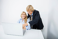Businesspeople discussing over laptop in office