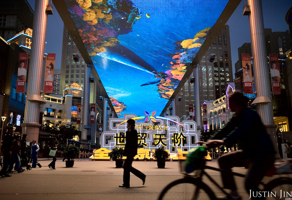 "People walk and cycyle past ""The Place"", a new open-air shopping mall with the biggest LCD screen in Asia as its roof."