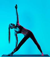 one caucasian woman exercising Trikonasana yoga exercices triangle pose  in silhouette studio isolated on blue background