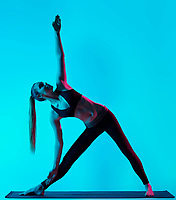 one caucasian woman exercising Trikonasana yoga exercices triangle pose  in silhouette studio isolated on blue background