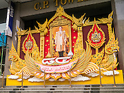 07 OCTOBER 2012 - BANGKOK, THAILAND:   A portrait of Bhumibol Adulyadej, the King of Thailand, in front of the C.P. Tower on Silom Road in Bangkok.  Bhumibol Adulyadej is the reigning King of Thailand. He is known as Rama IX. Having reigned since 9 June 1946, he is the world's longest-serving current head of state and the longest-reigning monarch in Thai history. He is revered by the Thai people, his birthday, Dec. 5, is a national holiday and is also celebrated as Father's Day in Thailand. As the King's Birthday approaches, businesses put up giant portraits of the King in front of their buildings.   PHOTO BY JACK KURTZ