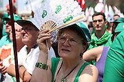 Woman supporter of Lega Nord (Northern League party) hold a fan with the ancient symbol of Lombardy region to protect herself from the sun at a meeting in Pontida, Sunday, June 14, 2009. ..