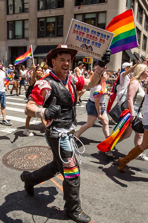 """New York, NY - 25 June 2017. New York City Heritage of Pride March filled Fifth Avenue for hours with groups from the LGBT community and it's supporters. Marchers from Gays Against Guns, including one dressed as a cowboy, with a sign reading """"Proud cowboy dont need no damn gun."""""""