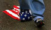 A protester drags an American flag wrapped about his shoe during a May Day parade through downtown Portland.