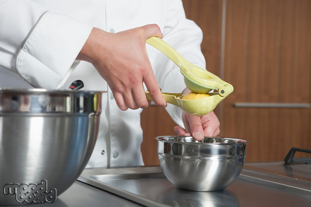 Mid- adult chef squeezing lemon