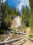 A woman enjoys sitting in Point Lace Falls on a beautiful summer day; Yoho National Park, near Golden, British Columbia, Canada