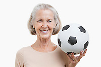 Portrait of senior woman holding soccer ball against white background