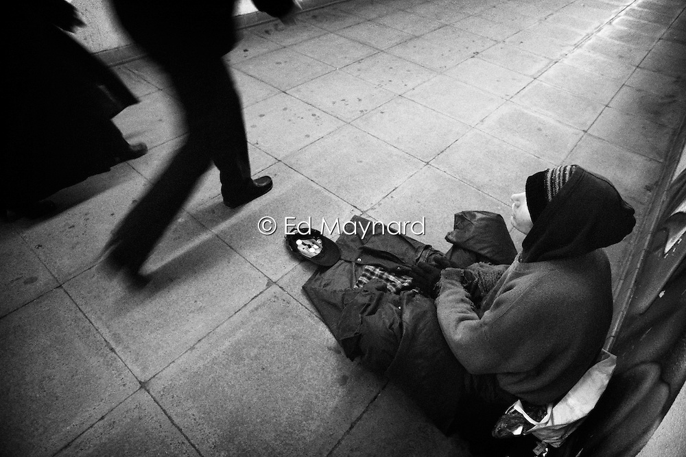 People walking past a homeless beggar sat on the pavement in a subway, Birmingham, West Midlands, England, UK.