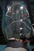 A visitor to the BAE Systems exhibition hall is handed a helmet in a mock-up of the Tempest fighter, a replacement for the Typhoon, in the company's exhibition hall at the Farnborough Airshow, on 18th July 2018, in Farnborough, England.