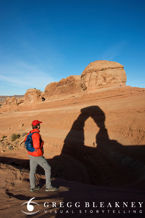 A hiker under Delicate Arch at sunrise - Arches National Park - Utah