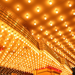 Picture of Chicago Theater exterior entrance lights at night. The Chicago Theatre is a Chicago landmark and is a popular venue for concerts, plays, and other live performances. Image is high resolution and is available as a stock photo, poster or print.