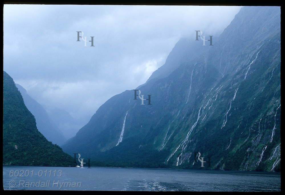 Towering walls of Milford Sound, teeming with waterfalls from recent storm, dwarf distant boats; Fiordland NP, New Zealand
